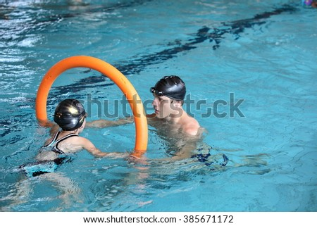 father playing with daughter in swimming pool - healthy lifestyle - stock photo