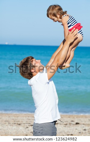 Father playing with daughter on the beach - stock photo