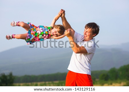Father playing with daughter on the camomile meadow - stock photo