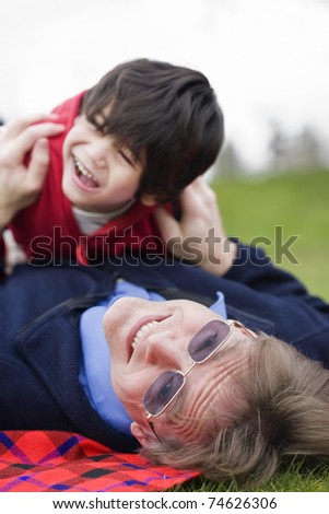 Father playing with disabled son on grass at park - stock photo