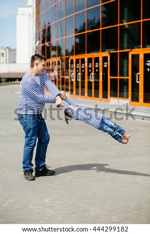 Father playing with his adorable young daughter, he holds her hands and circling - stock photo