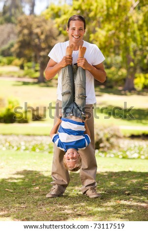 Father playing with his son  in the park - stock photo
