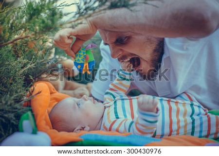 Father playing with his son lying on the lawn. - stock photo