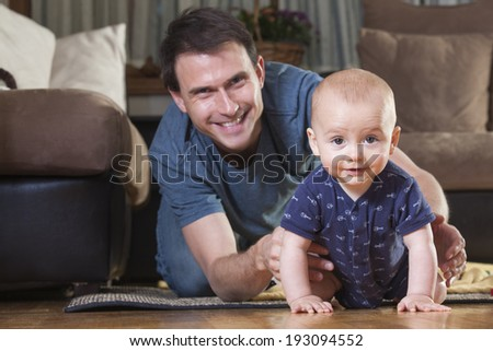 Father playing with his son on the floor  - stock photo