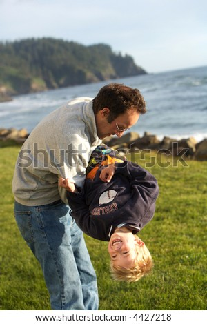 Father playing with his son outside at the beach - stock photo