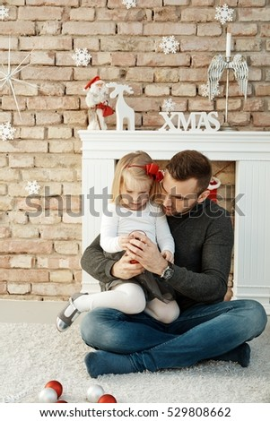 Father playing with little daughter at christmas time.