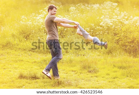 Father playing with son child having fun outdoors in sunny summer day - stock photo