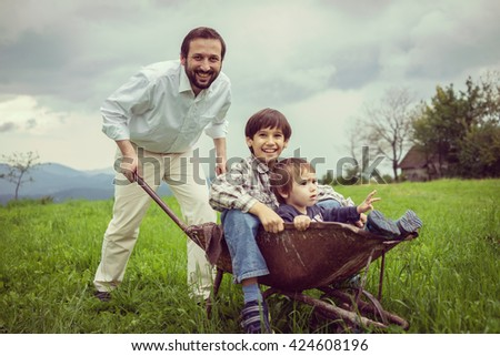 Father playing with sons using trolley on meadow