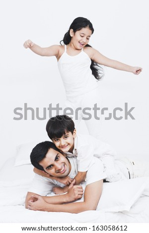 Father playing with their children on the bed - stock photo