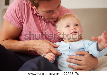 Father Playing With Young Son Indoors - stock photo