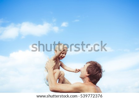 Father playing with young son lifting his hands up