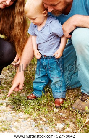 father pointing a rock to his toddler son in casual t-shirt and jeans on a nature walk with a mother - stock photo