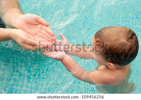 Father pouring water in hands of his son in the swimming pool on beautiful summer day. Focus is on hands. - stock photo