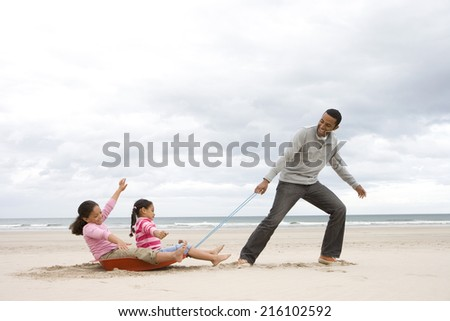 Father pulling daughters (5-9) on sledge on beach, side view - stock photo