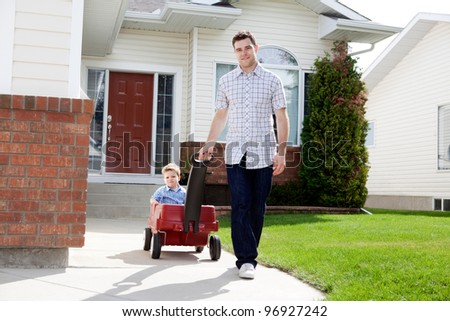 Father pulling son in a wagon in front of house on sidewalk - stock photo