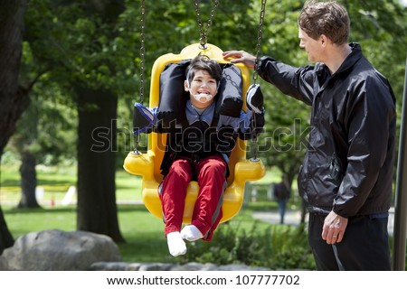 Father pushing disabled boy in special needs handicap swing. Child has cerebral palsy. - stock photo