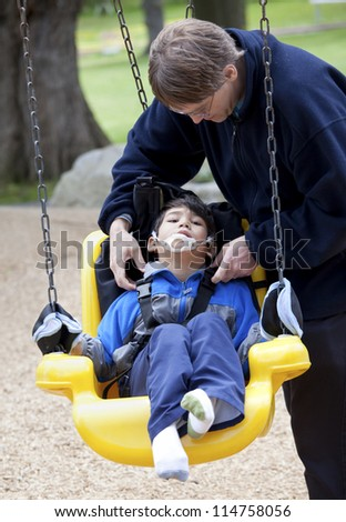 Father pushing disabled son  on yellow handicap swing - stock photo