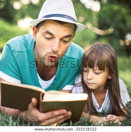 Father reading a book to his daughter while laying outdoor on the grass  - stock photo