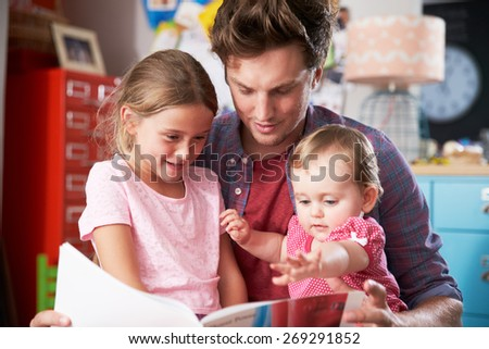 Father Reading Book With Daughters In Bedroom - stock photo