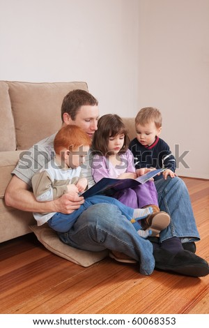 Father reading story to three kids sitting on his lap - stock photo