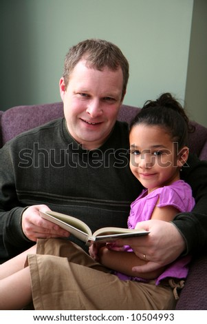 Father reads a book to his young daughter