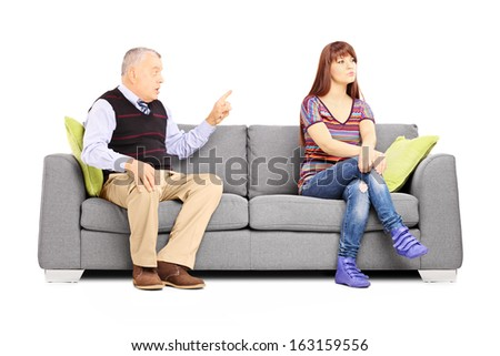 Father reprimending his uninterested daughter seated on a couch isolated on white background
