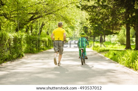 Father run with little boy, who rides a bike