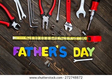 Father's day. Letters and tools on a wooden background.