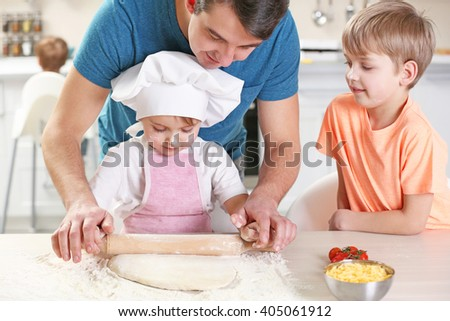 Father's hands helping his son to roll out a dough, close up - stock photo