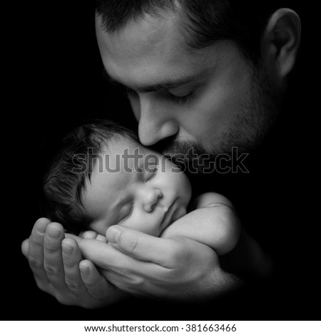 Father 's love.  Daddy kisses his newborn baby. Close-up portrait on a black background - stock photo