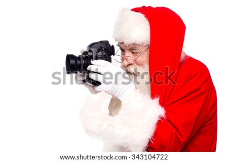 Father santa taking christmas picture - stock photo