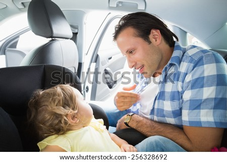 Father securing his baby in the car seat in his car - stock photo