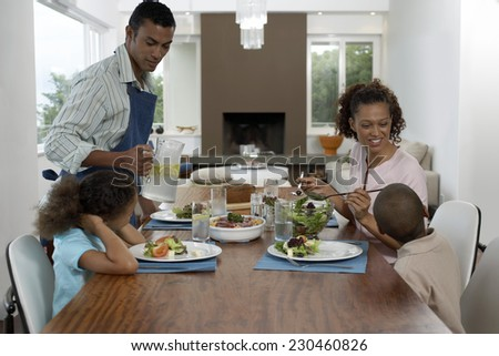 Father Setting the Dining Table with Family - stock photo