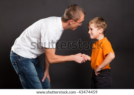 Father shakes hands with the son - stock photo