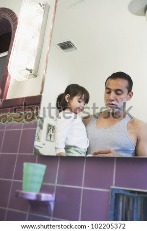 Father shaving with curious toddler girl