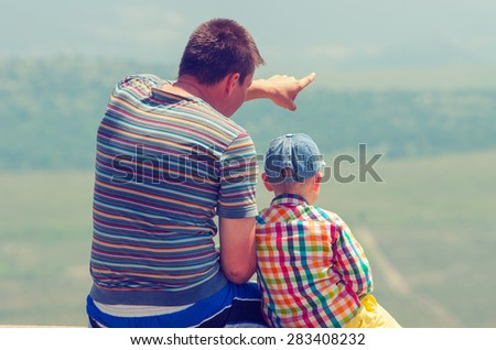 Father shows his son something in the distance. Vintage Family composition