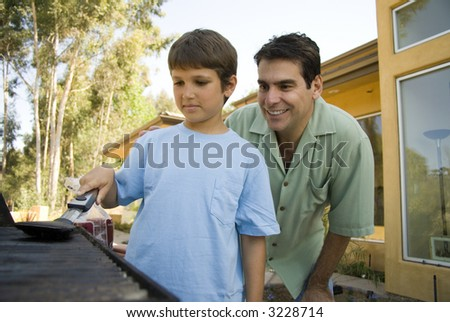 Father shows son about BBQ - stock photo