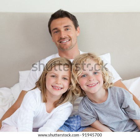 Father sitting on bed together with his children - stock photo