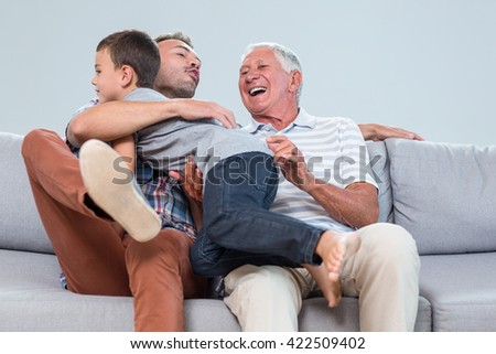 Father sitting on sofa with grandfather and embracing son in living room - stock photo