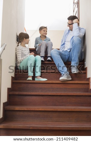 Father sitting with children on steps at home - stock photo