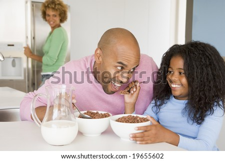 Father Sitting With Daughter As She They Eat Breakfast - stock photo