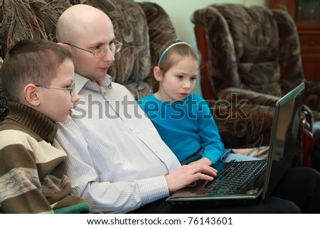 Father, son and daughter sitting on couch and look at laptop screen, serious faces, focus on boy