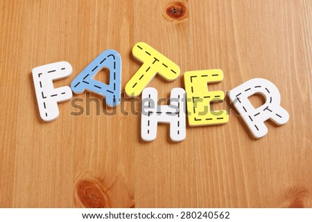 FATHER, spell by woody puzzle letters with woody background - stock photo