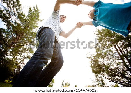 Father spinning son in park on a warm summer day - stock photo