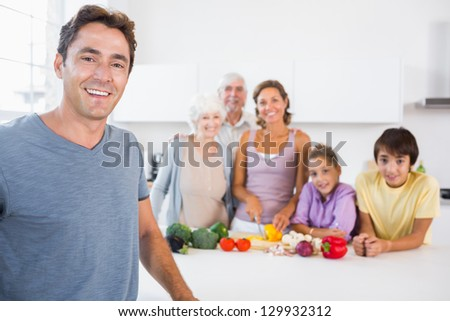 Father standing by kitchen counter with family behind him