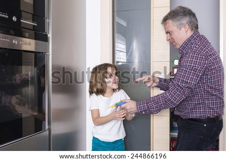 Father surprises his daughter taking candy - stock photo