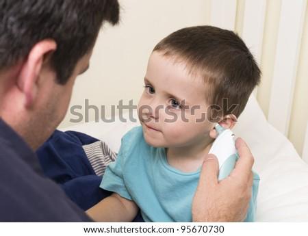 Father takes son's temperature - stock photo
