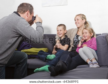 Father taking a photo of his family siting in the sofa