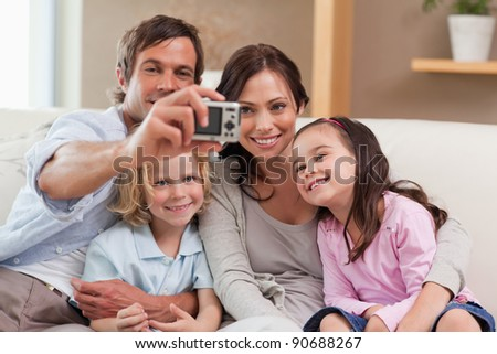 Father taking a picture of his family in the living room - stock photo