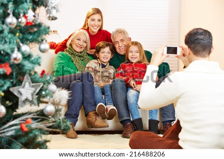 Father taking family picture at christmas with his smartphone - stock photo